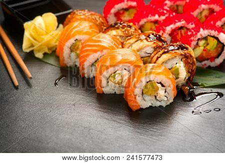Sushi with chopsticks and soy sauce. Sushi roll japanese food in restaurant. California Sushi roll set with salmon, vegetables, flying fish roe and caviar closeup. Japan restaurant menu