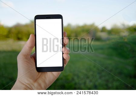 Modern Smartphone Device in man hand on summer green background. Mock up.