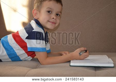 Close Up Little Boy Hand Writing On Paper, Notebook, Diary Kid Writing On Sofa In Living Room, Stude