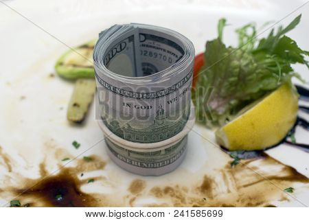 A Bundle Of Us Dollars On A Dirty Food Plate