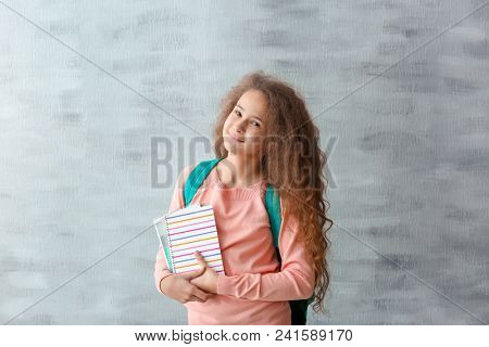 Stylish teenager with books against grey background