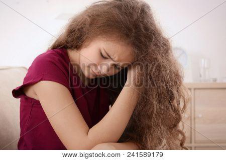 Depressed teenager sitting on sofa in room