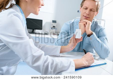 Doctor Holding Bottle Of Pills, Writing Diagnosis And Talking With Mature Patient In Clinic