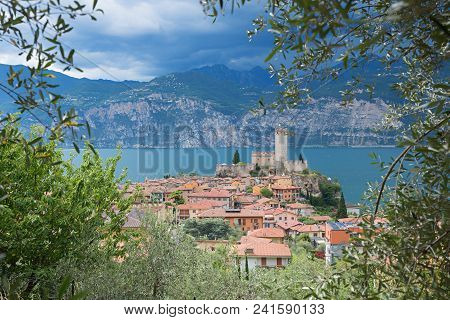 Beautiful View Through Olive Branches To Tourist Destination Malcesine And Garda Lake, North Italy