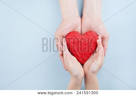Doctor And Kid Holding Red Heart In Hands Top View. Family Relationships, Health Care, Pediatric Car