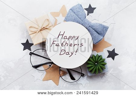 Happy Fathers Day Card Decorated Bowtie, Eyeglasses, Gift Box And Stars On Stone Table Top View In F