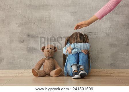 Female psychologist calming cute little girl indoors