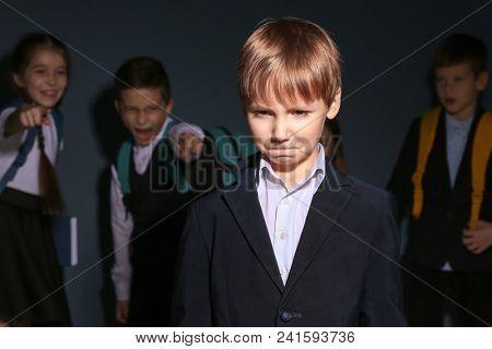 Children bullying their classmate on dark background
