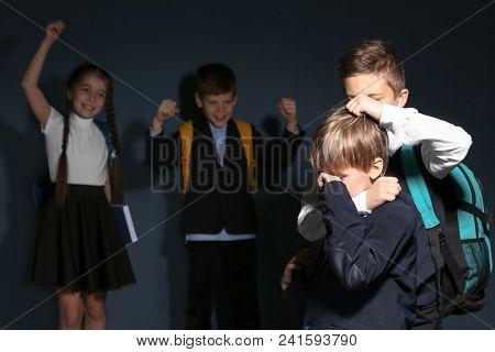 Little boy bullying his classmate on dark background