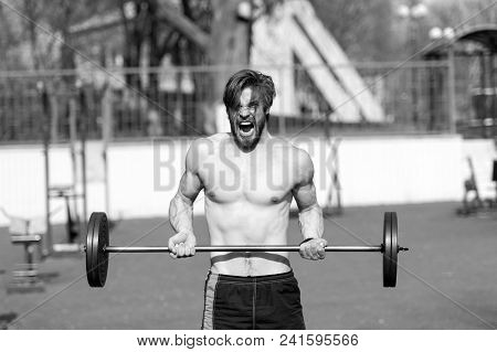 Sportsman Lift Barbell On Stadium. Man With Athletic Torso, Strong Arms. Athlete Shout Training With
