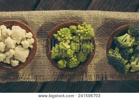 Table Top Shot Of Fresh Pieces Of Romanesco Broccoli, Broccoli And Cauliflower In Small Rustic Woode