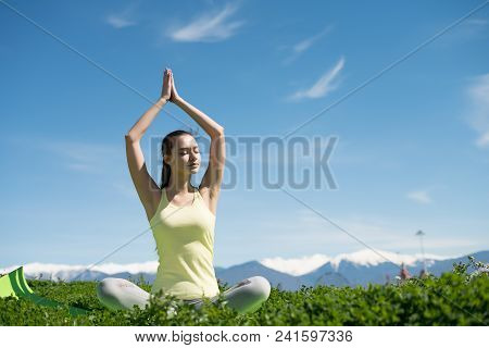 Peaceful Young Girl Meditates In Nature, Engaged In Yoga In The Sun