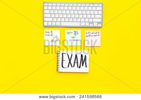 Exam Concept. Lettering Exam In Notebook On Student's Work Desk On Yellow Backgrond Top View Copy Sp