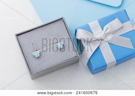 Butterfly Shape Earrings In Gift Box On Blue Background With Copy Space. Cute Jewelry For Child Girl