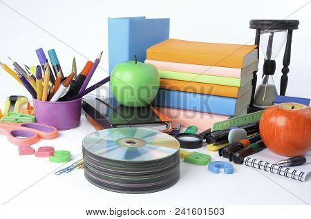 Stack Of Cds And School Supplies Isolated On White Background.photo With Copy Space.