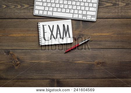 Preparing For The Exam. Word Exam Written In Notebook On Student's Desk With Computer On Dark Wooden