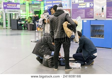 A Man At The Airport Rummages In Her Suitcases. A Man Is Looking For Things In Bags. The Man At The
