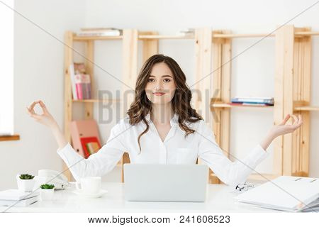 Business And Health Concept: Portrait Young Woman Near The Laptop, Practicing Meditation At The Offi