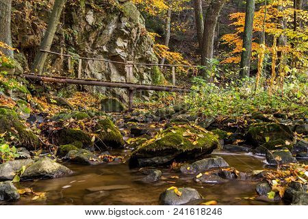 A Wooden Footbridge Over A Rocky Creek In Autumn