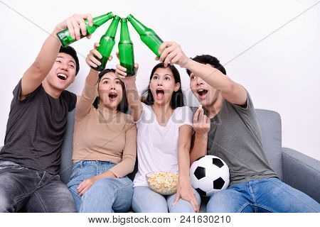 Concept Of Cheering. Asian Teenagers Watching Football On Television. People Are Cheering And Winnin
