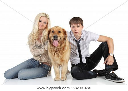 A Young Family With A Dog Sitting On Floor, Looking At Camera