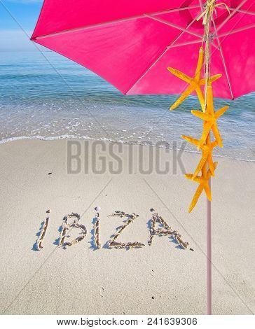 Pink Parasol Yellow Starfish Summer Theme And Ibiza Written In Sand On Beach In Ibiza, Spain
