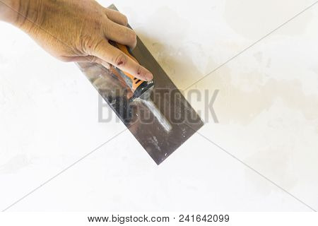 Close-up Of A Woman Hand With Metal Big Spatula, To Equalize The Plaster Filler On The Wall. Renovat