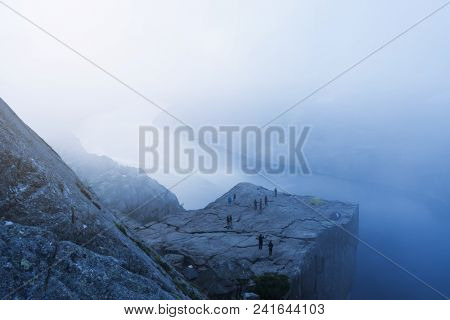 Cliff Preikestolen in fog at Lysefjord fjord, Norway
