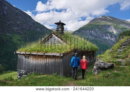 Kagefla - historic mountain farms on the mountainsides along the Geirangerfjorden fjord. Tourist attraction of Norway. A pair of travelers visiting traditional Scandinavian turf houses