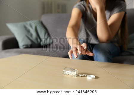 Depressed girl catching antidepressant pills sitting on a couch in the living room at home poster