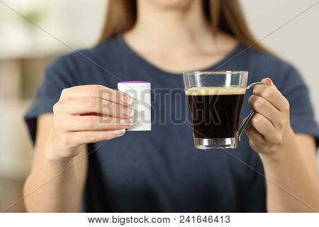 Front View Close Up Of A Woman Hands Holding A Coffee Cup And Saccharin At Home