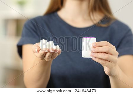Front View Close Up Of A Woman Hands Holding Sugar Cubes And Saccharin At Home