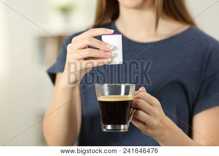 Front View Close Up Of A Woman Hands Throwing Saccharin Into A Coffee Cup At Home