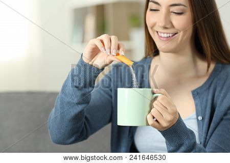 Close Up Of A Woman Hands Throwing Sugar Into A Mug Sitting On A Couch In The Living Room At Home