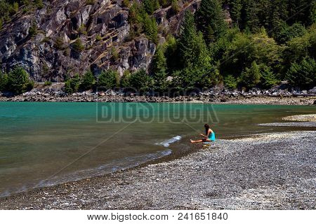 A Young Girl Sits At The Shore Of The Bay, A Wooded Cliff   On The Opposite Shore  Blue Sky, Porteau