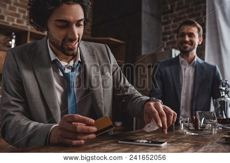 Close-up View Of Smiling Man In Suit Taking Drugs While Friend Standing Behind