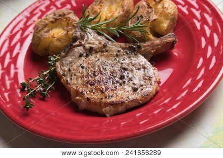 Spicy pork loin chop steak served over roasted potato