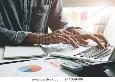 Close Up Of Businessman Or Accountant Hand Holding Pen Working On Laptop Computer For Calculate Busi