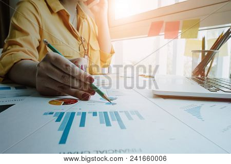 Close Up Businessman Hand Holding Pen And Pointing At Financial Paperwork With Financial Document