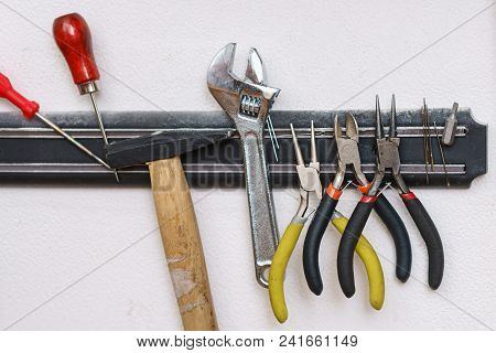 Set Of Tanner Tools Close-up. An Awl, Screwdriver, Hammer, Wrench, Pliers And Wire Cutters Hang On M
