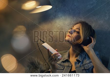 Young Attractive Girl Listening To Music On Headphones. She Sits On The Bed In The Bedroom And Holds
