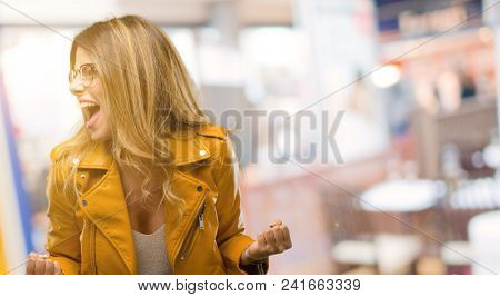 Beautiful young woman happy and excited celebrating victory expressing big success, power, energy and positive emotions. Celebrates new job joyful at restaurant