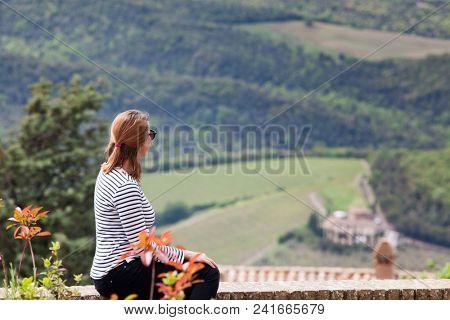 female traveler admiring tuscan landscape