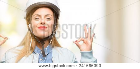 Young woman with bike helmet and earphones doing ok sign gesture with both hands expressing meditation and relaxation