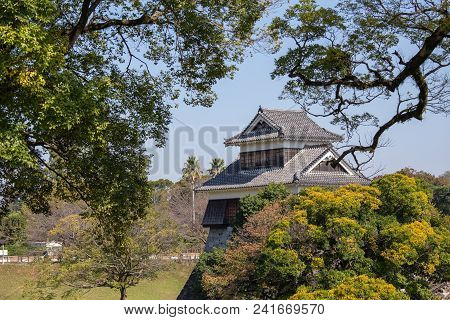wooden turret or yagura on stone wall of Kumamoto castle in Japan surround by green tree and blue sky with  copy space poster