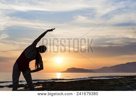 Young Girl Practicing Yoga On The Beach During The Sunset.