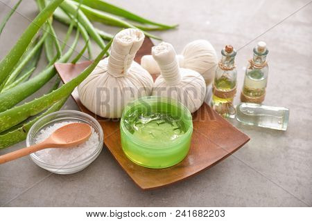 Spa setting with spoon, salt in bowl ,,bottle oil, aloe ,herbal, ball,on gray background