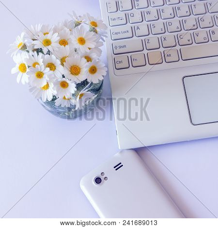Workspace With Computer At Home , A Desk With Flowers And White Smartphone. Woman's Modern Workspace