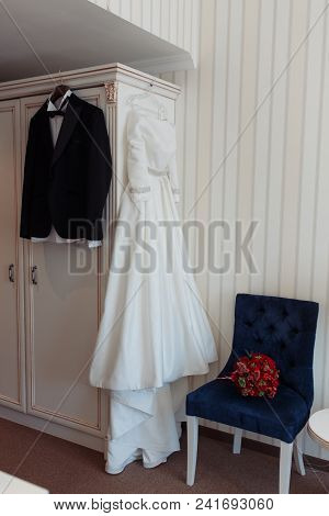Beautiful Black Grooms Jacket And Brides Dress Hanging In Hotel Room.