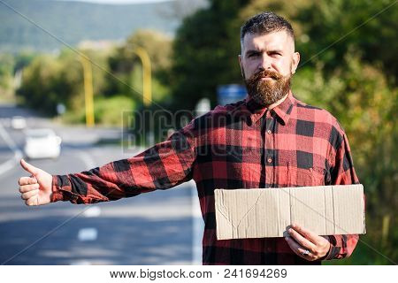 Man With Strict Face And Beard Travelling By Hitchhiking With Road On Background. Travelling And Hit